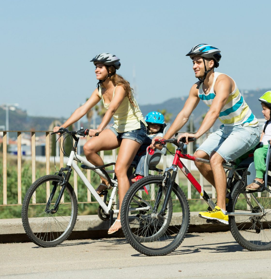 Young family with two little daughters traveling by bicycles. Focus on man